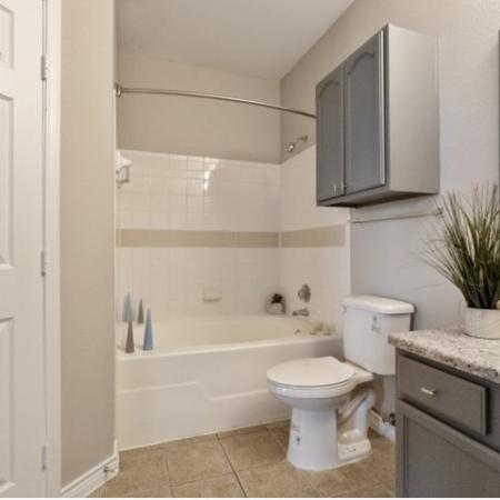 View of Renovated Apartment Interior, Showing Bathroom With Tile Flooring, Storage, and Single Vanity at Bluffs at Vista Ridge Apartments