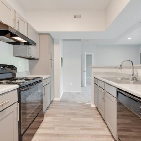 View of Renovated Apartment Interior, Showing Kitchen with Plank Wood Flooring, Breakfast Bar, and Gas Appliances at Waterford Creek Apartments