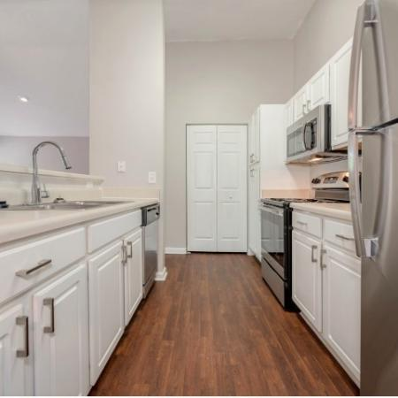 View of Renovated Apartment Interior, Showing Kitchen With Plank-Wood Flooring and Stainless Steel Appliances at Arbors at Fairview Apartments