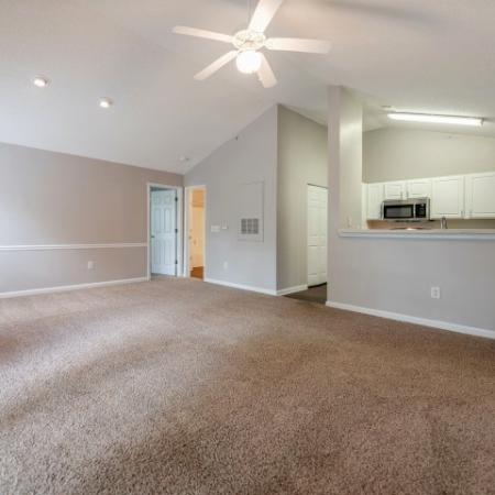 View of Renovated Apartment Interior, Showing Living Room With Ceiling Fan, Breakfast Bar, and View of Kitchen at Arbors at Fairview Apartments