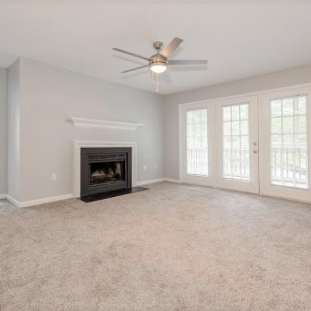 View of Renovated Apartment Interiors, Showing Living Room with Fireplace, Ceiling Fan, and Doors to Patio at Plantations at Haywood Apartments