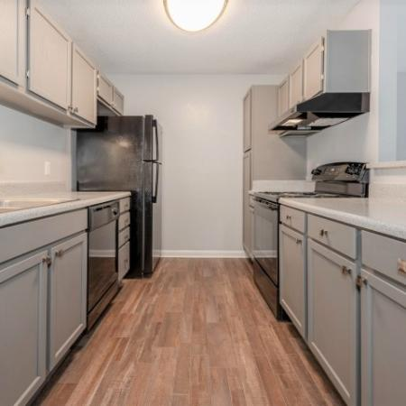 View of Renovated Apartment Interiors, Showing Kitchen with Gas Appliances and Wood Plank Flooring at Plantations at Haywood Apartments