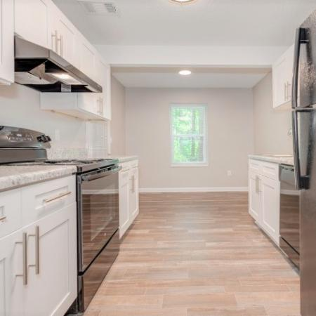 View of Renovated Apartment Interiors, Showing Kitchen with Plank Wood Flooring and Gas Appliances at Plantations at Haywood Apartments