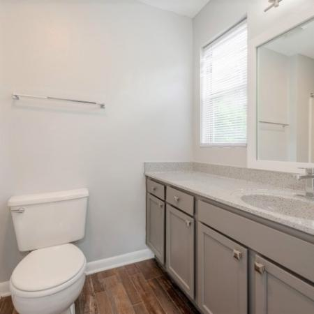 View of Renovated Apartment Interiors, Showing Bathroom with Granite Counter Top and Single Vanity at Plantations at Haywood Apartments