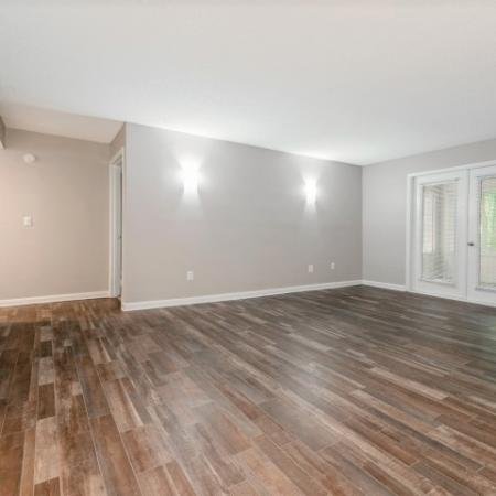 View of Renovated Apartment Interiors, Showing Living Room with Doors to Patio and Wood Plank Flooring at Plantations at Haywood Apartments