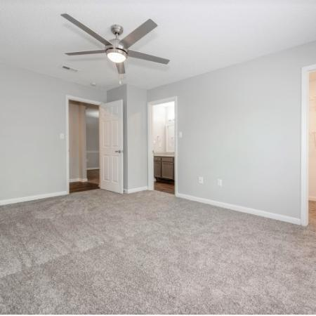 View of Renovated Apartment Interiors, Showing Bedroom with Ceiling Fan, View to Closet and Bathroom at Plantations at Haywood Apartments