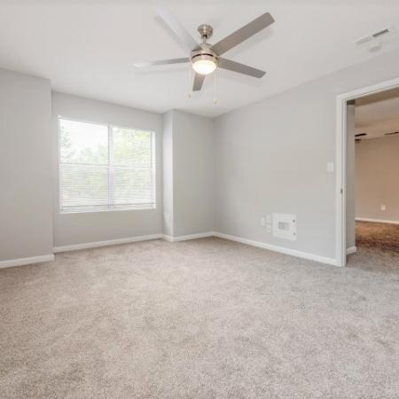 View of Renovated Apartment Interiors, Showing Bedroom with Ceiling Fan, Window View, and View to Living Room at Plantations at Haywood Apartments