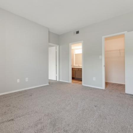 View of Renovated Apartment Interior, Showing Bedroom with Modern Paint, View of Closet and Bathroom at Waterford Creek Apartments