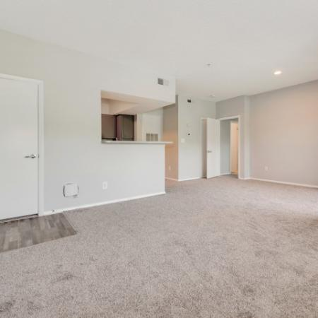 View of Renovated Apartment Interior, Showing Living Room with Modern Paint, Plank Wood Flooring, and View of Kitchen at Waterford Creek Apartments