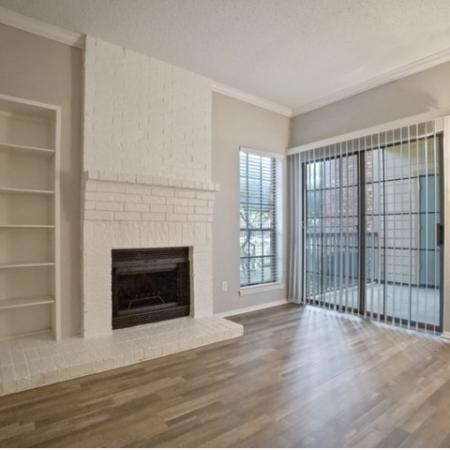 View of Renovated Apartment Interior, Showing Living Room with Plank Wood Flooring and Glass Sliding Door at The Oaks of North Dallas Apartments