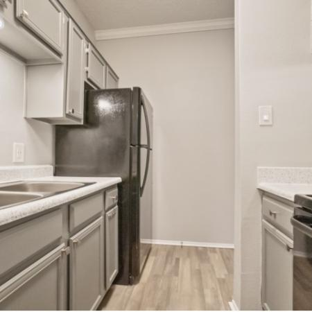 View of Renovated Apartment Interior, Showing Kitchen with Gas Appliances and Plank Wood Flooring at The Oaks of North Dallas Apartments