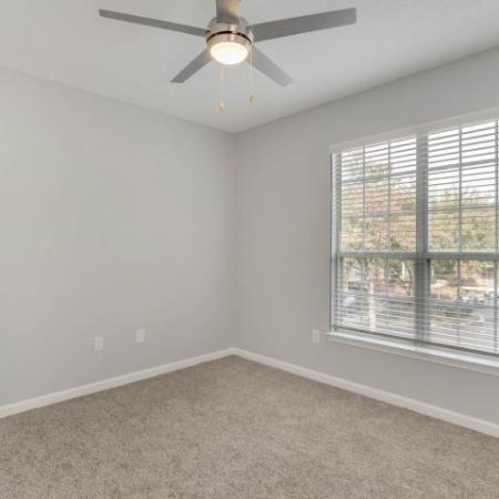 View of Bedroom, Showing Unfurnished Bed, Ceiling Fan, Carpet, and Window at Retreat at River Park Apartments