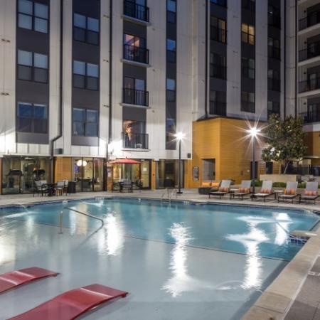 View of Pool, Showing Loungers, Outdoor Furniture, and Apartment Building in Background at Cottonwood Westside Apartments