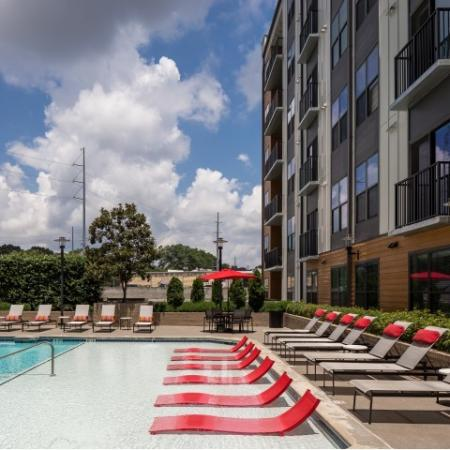 View of Pool, Showing Loungers, Picnic Areas, and Apartment Building to Left at Cottonwood Westside Apartments