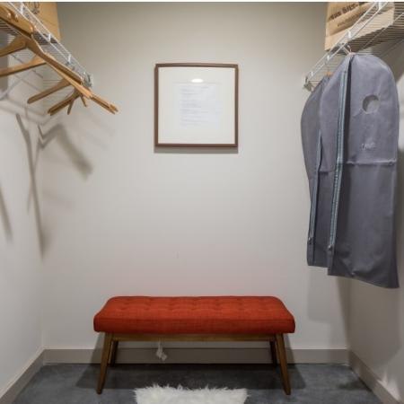 View of Walk-In Closet, Showing Hangers, Bench, and Bags at Cottonwood Westside Apartments