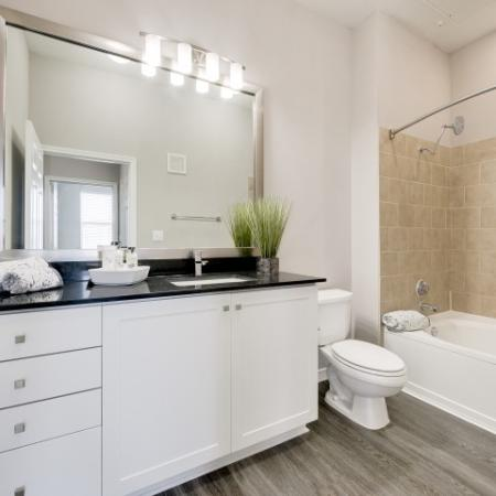 View of Renovated Apartment Interior, Showing Bathroom With Granite Counter Top, Single Vanity, and Garden Tub at McKinney Uptown Apartments