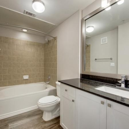 View of Renovated Apartment Interior, Showing Bathroom With Single Vanity and Granite Counter Top at McKinney Uptown Apartments