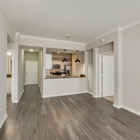 View of Renovated Apartment Interior, Showing Living Room With Plank Wood Flooring, View of Kitchen and Bathroom at McKinney Uptown Apartments