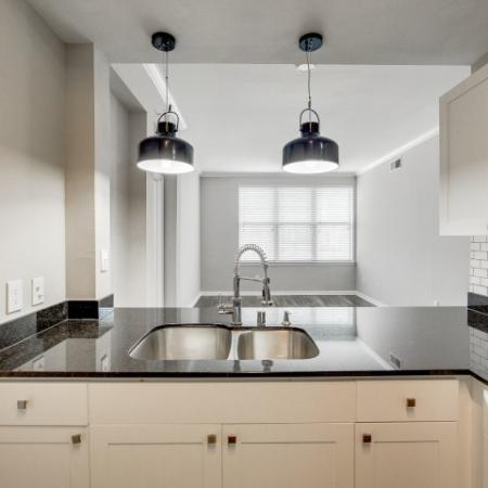 View of Renovated Apartment Interior, Showing Kitchen With Granite Counter Top, Overhead Lights, and View of Kitchen at McKinney Uptown Apartments