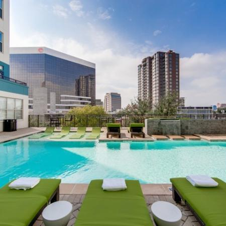 View of Pool Area, Showing Loungers and View of Apartment Buildings at McKinney Uptown Apartments
