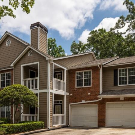 Image of apartment building exterior at Retreat at Peachtree City showcasing attached garages and  private patio and balcony
