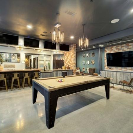 View of Resident Lounge, Showing Pool Table, Seating Areas, Counter Stools, and TV at 935M Apartments