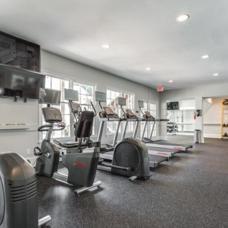 View of Fitness Center, Showing Cardio Machines, TV, and Window Views at Plantations at Haywood Apartments