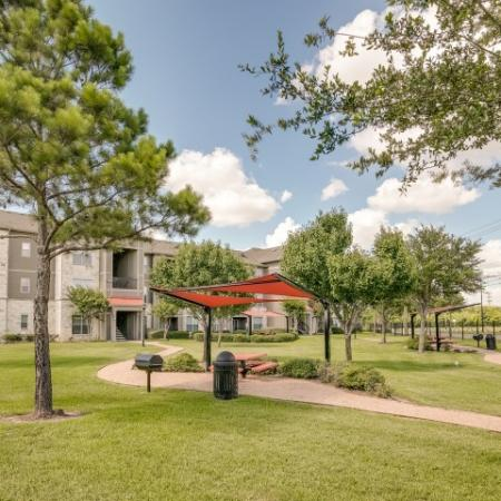 View of Common Green Space, Showing Trees, Building Exterior, Benches and Covered Shaded Area at Retreat at Stafford Apartments