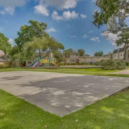 View of Basketball Court, Showing Basketball Hoops, Grass, and Playground in Background at The Regatta Apartments