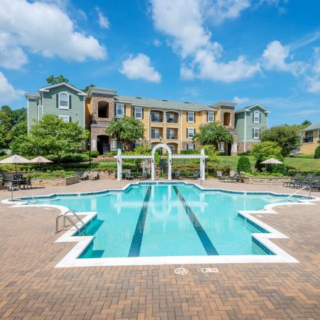 View of Resort Style Pool, Showing Seating With Umbrellas, Buildings, and Pergola at Cottonwood Reserve Apartments