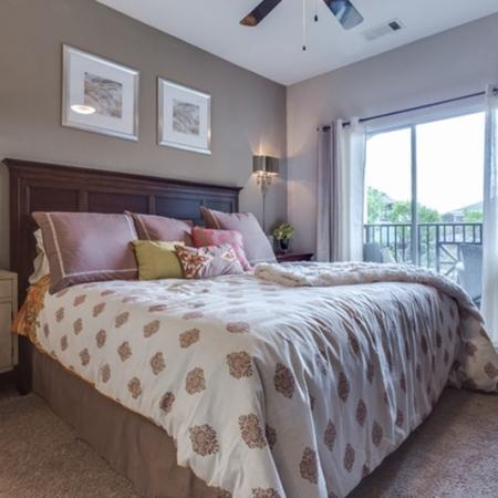 View of Classic Apartment Interiors, Showing Furnished Bedroom, Ceiling Fan, and View Onto Private Balcony at Cottonwood Reserve Apartments