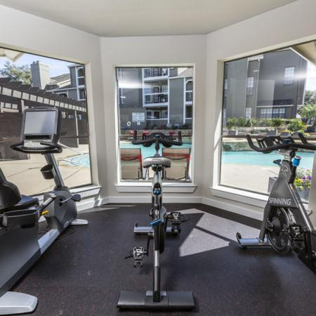 View of Fitness Center, Showing Stationary Bikes and A View of The Pool at The Arbors of Las Colinas Apartments