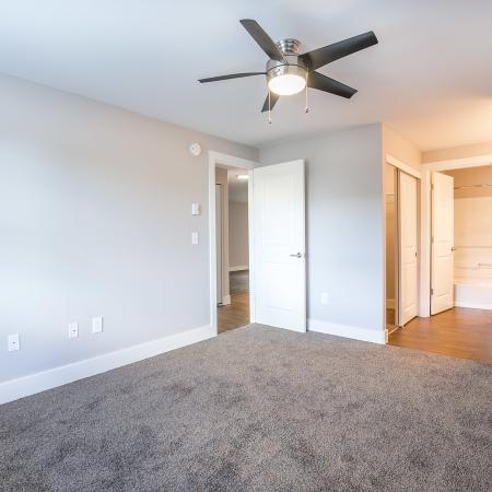 View of Renovated Apartment Interior, Showing Bedroom with Ceiling Fan, Carpet, Attached Bathroom, and Walk-In Closet at Scott Mountain Apartments