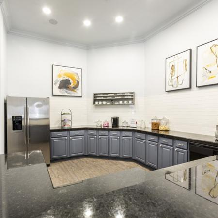 View of Renovated Community Kitchen, Showing Granite Countertops, Stainless Appliances, Snack and Coffee Bar at Stonebriar of Frisco Apartments