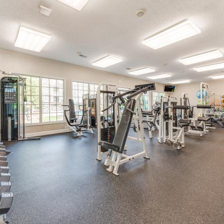 View of Fitness Center, Showing Free Weights, Weight Benches, Stability Balls, and Wall of Windows at Waterford Creek Apartments