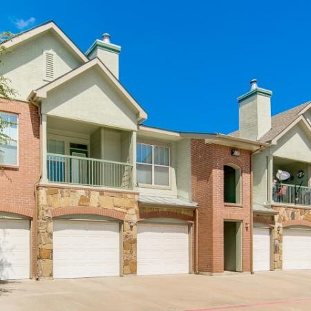 View of 2-Story Building Exterior, Showing Attached Garages and Private Patio or Balcony at Bluffs at Vista Ridge Apartments