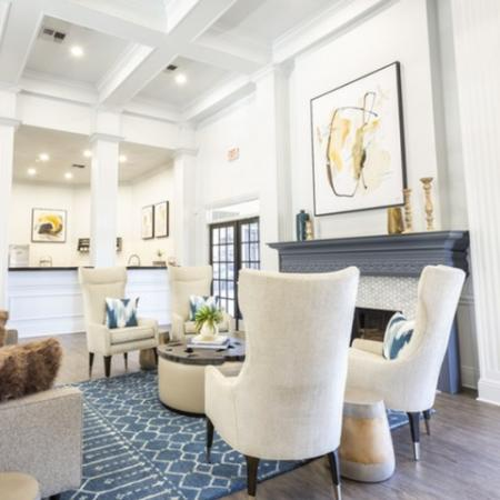 View of Renovated Clubhouse, Showing Seating Area, Plank Flooring, Fireplace, and Community Kitchen at Stonebriar of Frisco Apartments