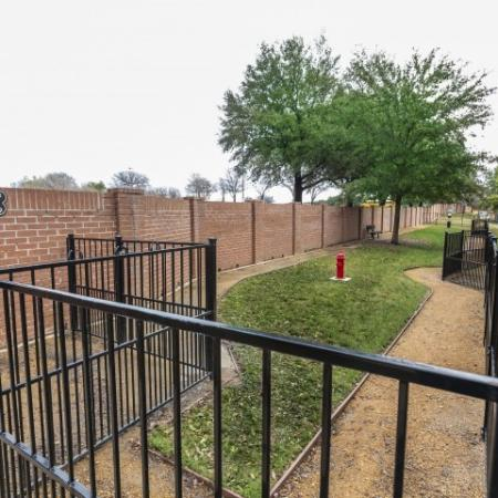 View of Fenced Dog Park, Showing Long Grassy Run, Bench, Fire Hydrant, and Pet Station at Bluffs at Vista Ridge Apartments