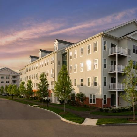 View of Community Exterior at Dusk, Showing 4-Story Building, Private Patio or Balcony, and Landscaping at Cottonwood One Upland Apartments