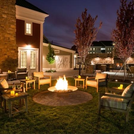 View of Firepit, Showing Chairs, Tables, and Clubhouse Exterior at Night at Cottonwood One Upland Apartments