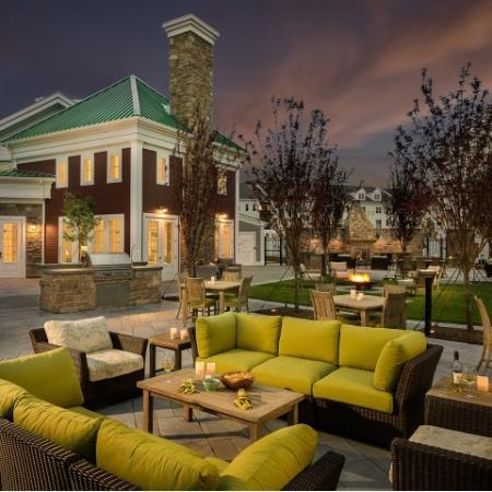View of Outdoor Lounge, Showing Couches, Tables, Grill, and Clubhouse Exterior at Dusk at Cottonwood One Upland Apartments