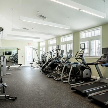 View of Fitness Center, Showing Cardio Equipment, Weight Benches, and Wall of Windows at Cottonwood One Upland Apartments