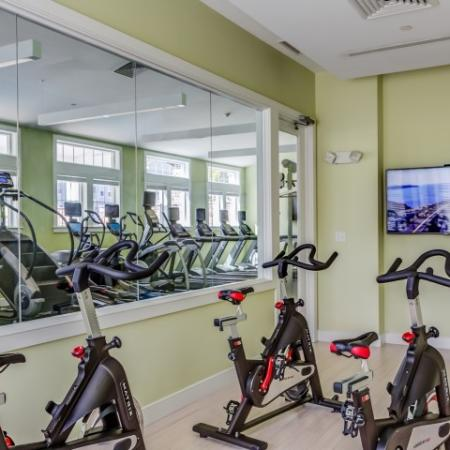 View of Private Spin Studio, Showing Bikes, Mirros, and Flat Screen TV For Peloton Classes at Cottonwood One Upland Apartments