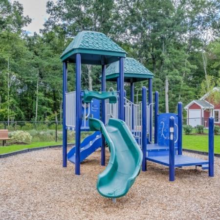 View of Playground, Showing Slide, Greenspace, and Bench at Cottonwood One Upland Apartments