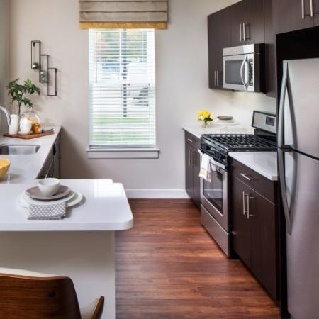View of Kitchen, Showing Quartz Countertops, Plank Flooring, Stainless Steel Appliances With Gas Range at Cottonwood One Upland Apartments
