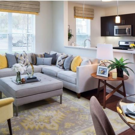 View of Furnished Living Room, Showing Couches, Large Windows, and View Into Kitchen at Cottonwood One Upland Apartments