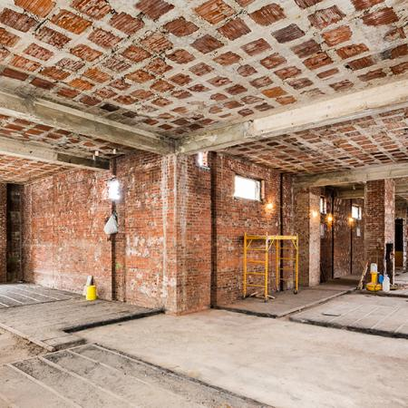 L shaped room with exposed brick during renovation