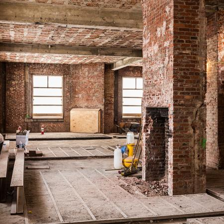 Well lit room surrounded by windows and adorned in exposed brick during renovation