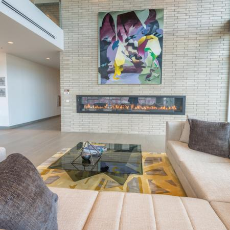 Sectional sofa strategically placed near floor to ceiling windows and fire place