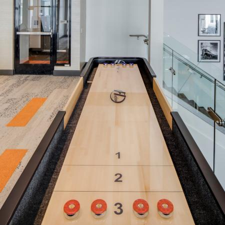 Resident Lounge featuring a Shuffleboard table next to glass encased stairway